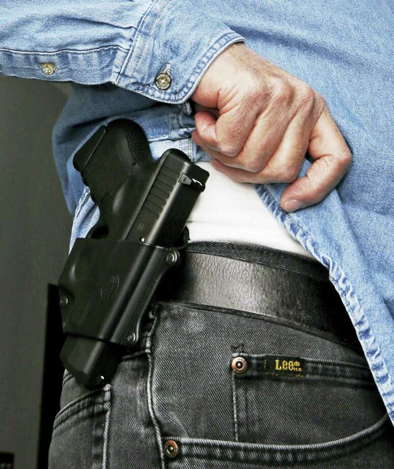 Hank Johnson displays his handgun, in Springboro, Ohio. Dealing a blow to gun supporters, a federal appeals court ruled Thursday, June 9, 2016, that Americans do not have a constitutional right to carry concealed weapons in public. Photo: AP Photo — Al Behrman, File / Copyright 2016 The Associated Press. All rights reserved. This material may not be published, broadcast, rewritten or redistribu