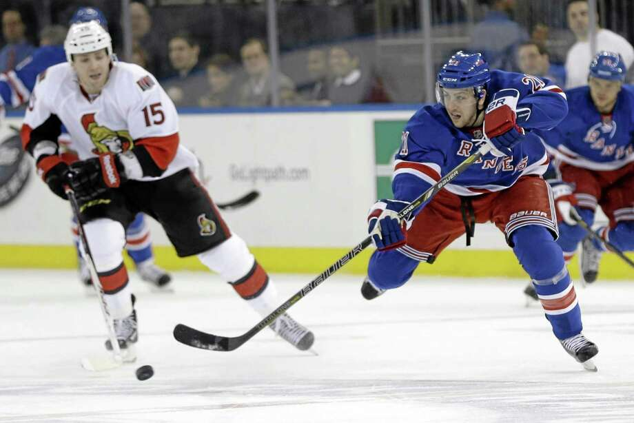 New York Rangers' Derek Stepan (21) passes the puck away from Ottawa Senators' Zack Smith (15) during the first period of an NHL hockey game Friday, March 8, 2013, in New York. Photo: AP Photo/Frank Franklin II  / AP