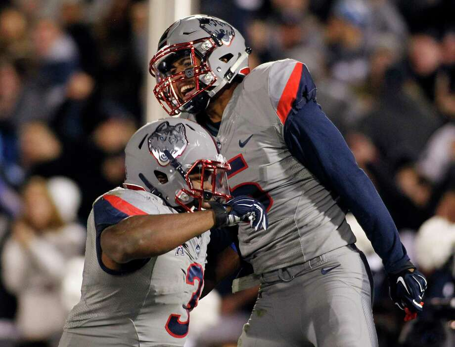 UConn running back Ron Johnson (3) celebrates a touchdown by wide receiver Noel Thomas, right, during the fourth quarter against Houston on Saturday. Fullback Garrett Anderson, not pictured, threw the touchdown pass. Photo: Stew Milne — The Associated Press  / FR56276 AP