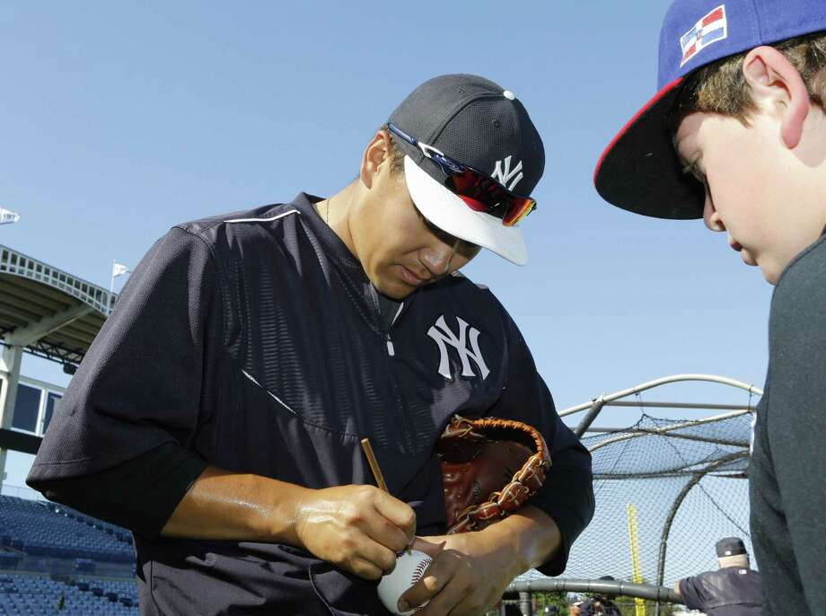 New York Yankees starter Masahiro Tanaka autographs a ball for a young fan before a spring training game last week in Tampa, Fla. Photo: Kathy Willens — The Associated Press  / AP