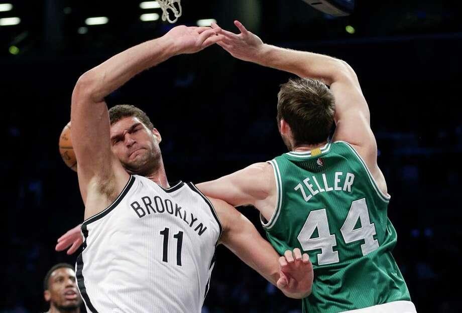 Nets center Brook Lopez blocks a shot by Celtics center Tyler Zeller during the third quarter Sunday. Photo: Julie Jacobson — The Associated Press  / AP