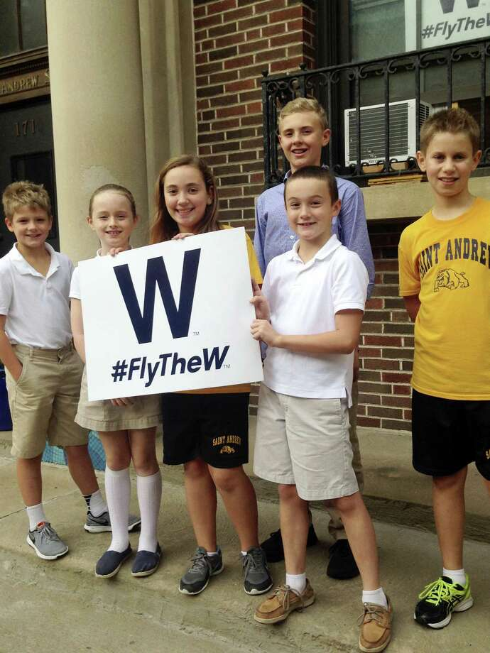 Students at Hawthorne Elementary School near Wrigley Field in Chicago hold a Cubs W sign outside the school. Photo: The Associated Press  / Copyright 2016 The Associated Press. All rights reserved.