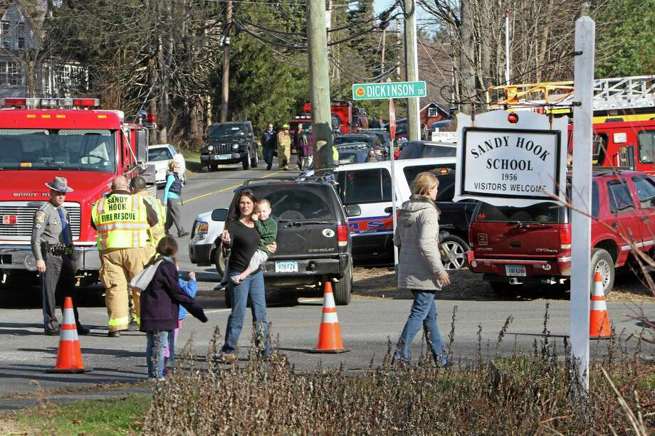 Parents walk away from the Sandy Hook  Elementary School with their children following a shooting on Friday, Dec. 14, 2012 in Newtown, Conn. Adam Lanza opened fire inside the Connecticut elementary school where his mother worked killing 26 people, including 18 children, and forcing students to cower in classrooms and then flee with the help of teachers and police. Photo: AP Photo/The Journal News, Frank Becerra Jr.  / The Journal News