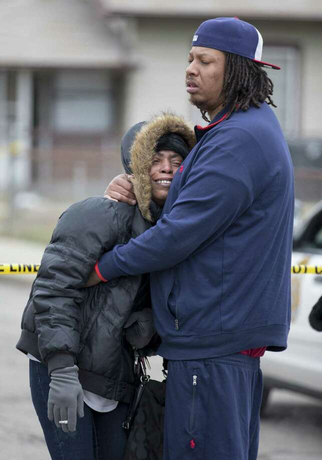 Carmon Lisenby, left, and Corey Bryant, both family members, console each other near a home at 3145 North Harding Street St. in Indianapolis, at a scene involving four homicide victims, Tuesday, March 24, 2015. Indianapolis Police Chief Rick Hite says three women and a man have been shot to death in the home. Hite says the shootings don't appear random and likely occurred Tuesday morning. (AP Photo/The Indianapolis Star, Robert Scheer)  NO SALES Photo: AP / The Indianapolis Star