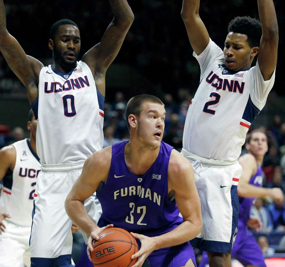 UConn's Phil Nolan (0) and Jalen Adams (2) defend Furman's Matt Rafferty (32) during the first half of the 19th-ranked Huskies' 83-58 win on Saturday at Gampel Pavilion. Photo: Michael Dwyer — The Associated Press  / AP