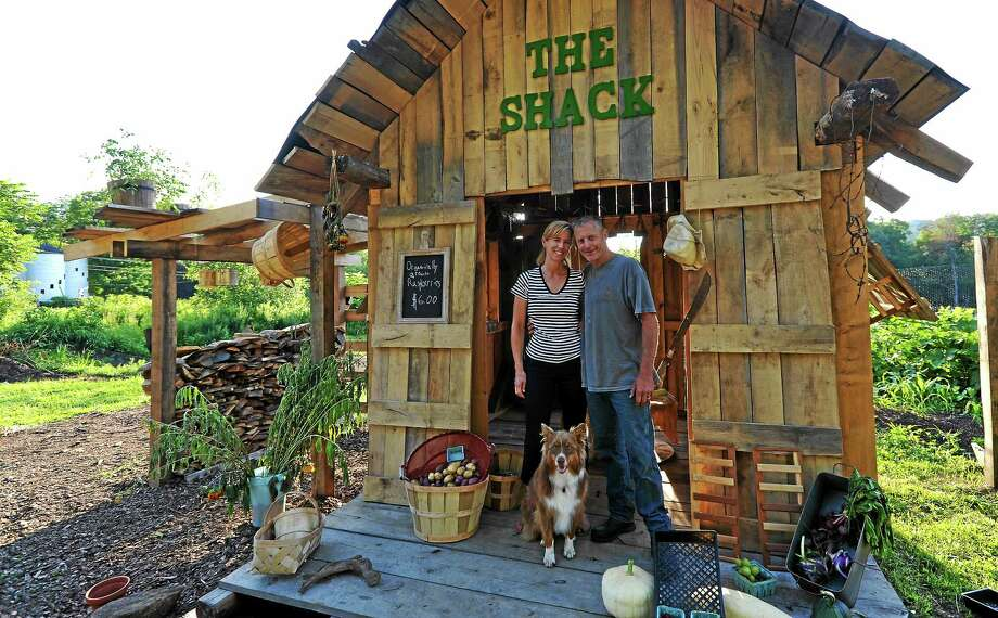 Amy and Bill Finnegan, with Finn, at Finnegan's Farm West stand at 55 Upland Road in New Milford. Photo: John Fitts — The Register Citizen