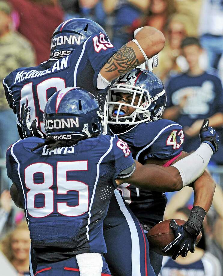 Sean McQuillan (49) celebrates with Lyle McCombs (43) and Geremy Davis (85) after a McCombs touchdown in a 2013 game. Photo: The Associated Press File Photo  / AP2013