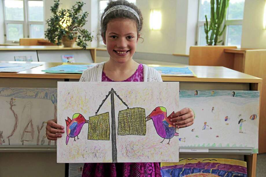 Amelia Ficalori shows her winning poster in the 2015 Peace Poster Contest. Photo: Register Citizen File Photo