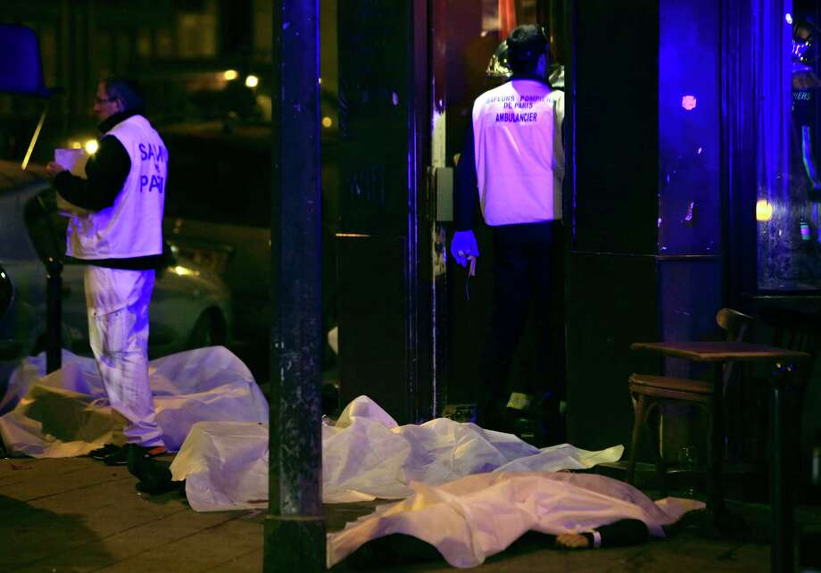 FILE -- In this  Friday, Nov. 13, 2015 file photo, victims lay on the pavement outside a restaurant after an attack claimed by the Islamic State group, in Paris France. The al-Qaida-claimed attack on a Mali hotel may have been partly aimed at asserting the global terror network's relevance as it faces an unprecedented challenge from the Islamic State group for leadership of the global jihadi movement. While the two groups share similar goals they have been bitterly divided over strategy and leadership, and have come to blows in Syria.  (AP Photo/Thibault Camus, File) Photo: AP / AP