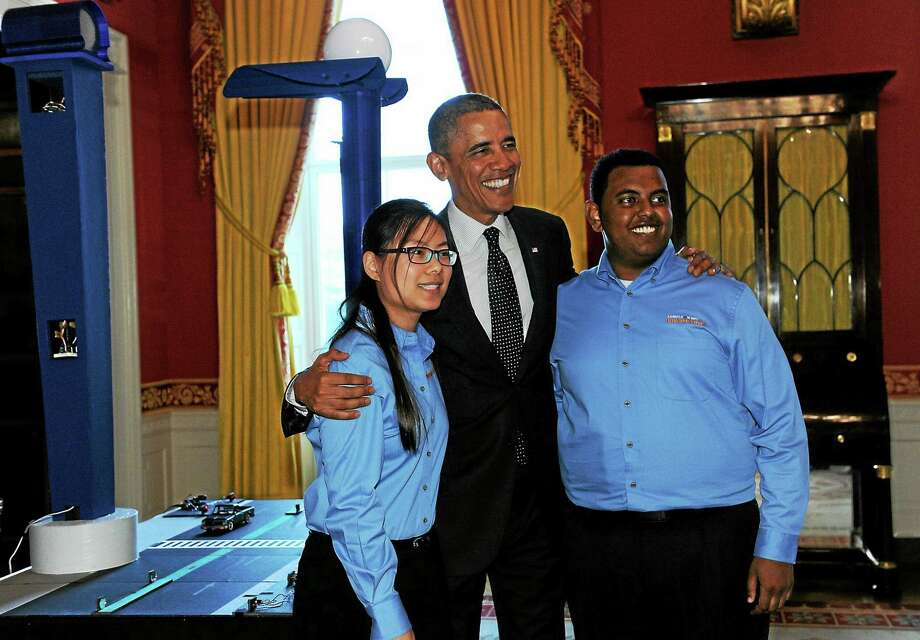 President Barack Obama poses with Karen Fan, 17, left, and Felege Gebru, 18, both of Newton, Mass., as the president toured the 2014 White House Science Fair exhibits on display in the State Dining Room of the White House on May 27, 2014. Obama was celebrating the student winners of a broad range of science, technology, engineering and math (STEM) competitions from across the country. Photo: AP Photo/Susan Walsh  / AP