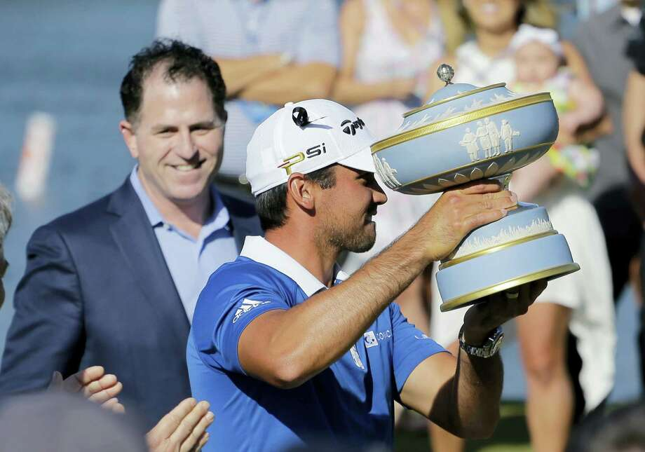 Jason Day holds his trophy after defeating Louis Oosthuizen in the final round the Dell Match Play Championship golf tournament at Austin County Club, Sunday. Dell CEO Michael Dell, left, made the presentation. Photo: By The Associated Press  / AP