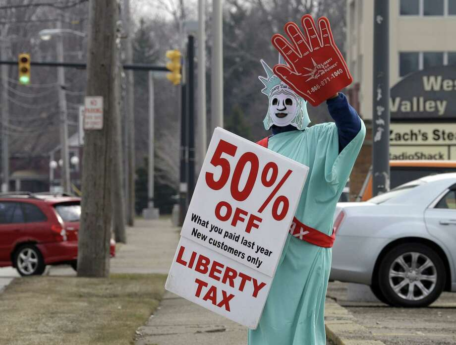 In this March 21, 2015 photo, Brittney Freison, dressed as Lady Liberty, waves to motorists near the Liberty Tax Service office in Berea, Ohio. Wary of rising fees, federal regulators are eyeing ways they can assert tighter oversight upon paid tax preparers who cater to an expanding market of cash-strapped families anxious for their tax refunds. Photo: AP Photo/Mark Duncan  / AP