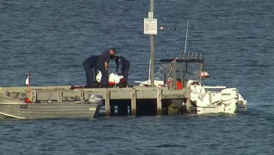In this image taken from video, police carry a body in a bag and place it in on a stretcher on a jetty in Triabunna, off the Australian island state of Tasmania, on Saturday, July 25, 2015. A woman watched her father being mauled to death by a large shark on Saturday while the pair were diving, police said. Photo: AuBC Via AP / AuBC