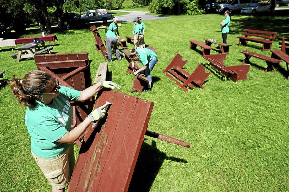 Volunteers from Berkshire Bank work to refinish picnic tables at Hancock Shaker Village. Photo: Ben Garver — The Berkshire Eagle