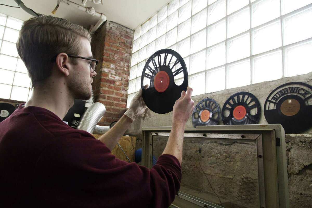 Will Haude examines a record that he has passed through a laser cutter at Wrecords By Monkey.