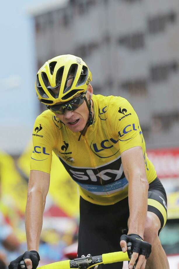 Chris Froome, wearing the overall leader's yellow jersey, crosses the finish line of the nineteenth stage of the Tour de France on Friday. Photo: Christophe Ena — The Associated Press  / AP