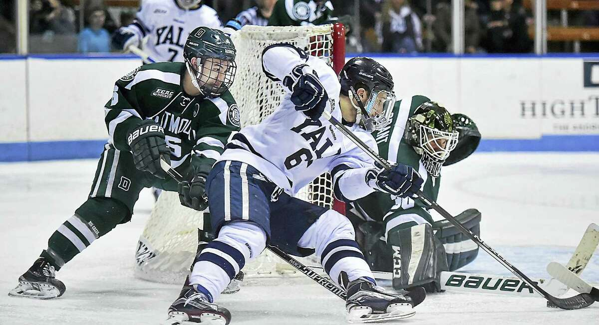 Yale's Stu Wilson tries to sneak one past Dartmouth goalie Charles Grant during a game earlier this season.
