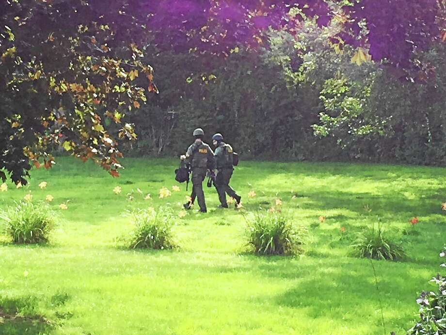 Police walk through a backyard near the house on Torringford Street in Torrington where a man is believed to be barricaded with a weapon. Photo: Ben Lambert — The Register Citizen