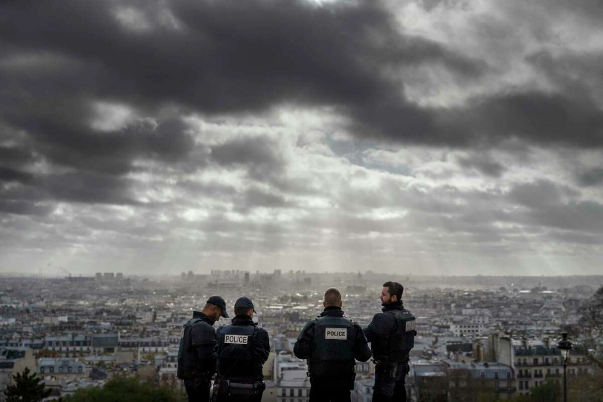French Police officers stand on guard near the church of Sacre Coeur, on top of the Montmartre hill with Paris, Wednesday, Nov. 18, 2015. A woman wearing an explosive suicide vest blew herself up Wednesday as heavily armed police tried to storm a suburban Paris apartment where the suspected mastermind of last week's attacks was believed to be holed up, police said.