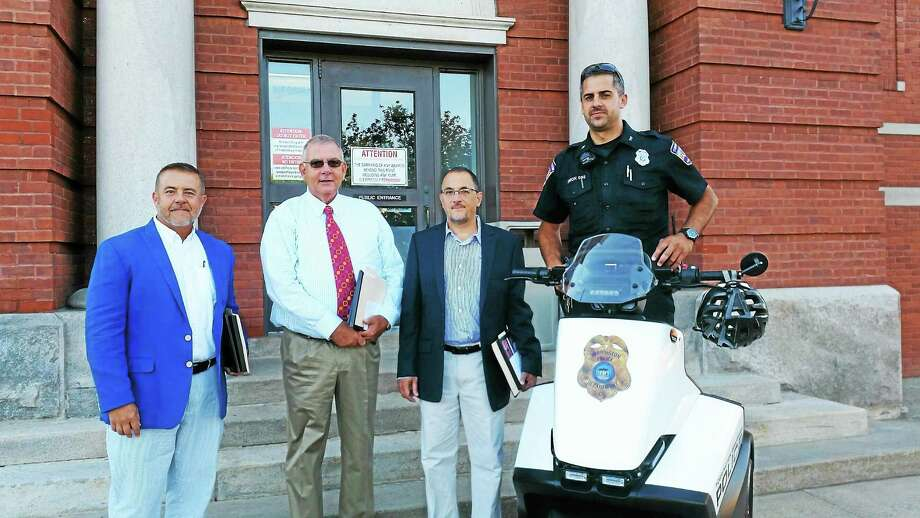 Officer Rob Simon stands on his Segway with John Capobianco, Tom Barron and Bill Zampaglione. The Segway was purchased with donated funds from three businesses in Torrington. Photo: Amanda Webster — The Register Citizen