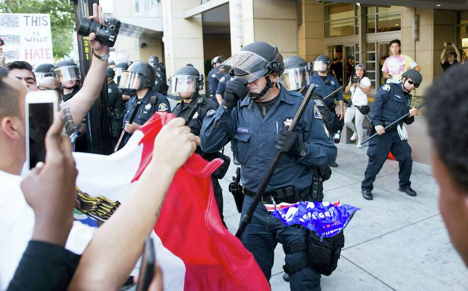 A police officer shields his face as protesters throw objects at officers outside a campaign rally for Republican presidential candidate Donald Trump on Thursday in San Jose, California. A group of protesters attacked Trump supporters who were leaving the candidate's rally in San Jose on Thursday night. Photo: ASSOCIATED PRESS  / FR34727 AP