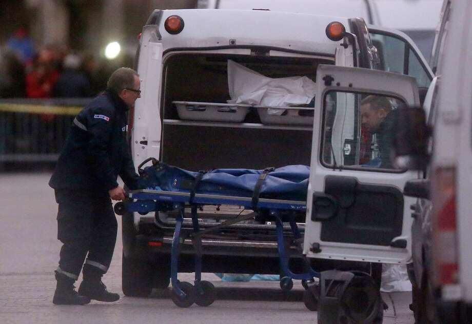 Two men carry a stretcher with a dead body into a hearse after an intervention of security forces against a group of extremists in Saint-Denis, near Paris, Wednesday, Nov. 18, 2015. A woman wearing an explosive suicide vest blew herself up Wednesday as heavily armed police tried to storm a suburban Paris apartment where the suspected mastermind of last week's attacks was believed to be holed up, police said. Photo: AP Photo/Michel Euler   / AP