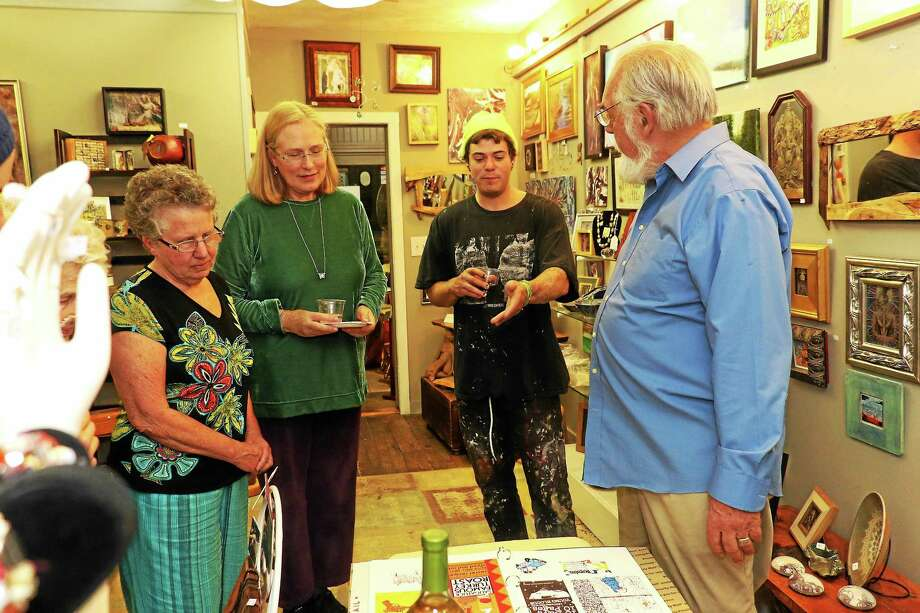 "The Artists' Path has announced it is closing its doors in December. Here Jeff Martin shows his design portfolio during the opening of ""Contained"" at the Artists' Path. From left are owner Lori Barker, Fran Clem, Martin and owner Ernie Barker. Photo: John Fitts – The Register Citizen"