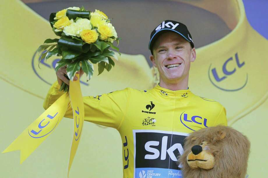 Chris Froome, wearing the overall leader's yellow jersey, celebrates on the podium of the eighteenth stage of the Tour de France on Thursday. Photo: Christophe Ena — The Associated Press  / AP