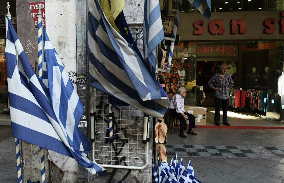 Shop owners wait for customers in Athens on July 23, 2015. Greece's radical left-led government emerged bloodied but alive early Thursday from a key vote in parliament, which overwhelmingly approved new creditor-demanded reforms despite a revolt among hardliners in the main coalition partner. Photo: AP Photo/Giannis Papanikos  / AP