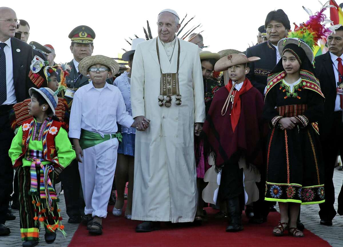 In this Wednesday, July 8, file photo, Pope Francis holds hands with children wearing traditional clothing as he walks with Bolivian President Evo Morales, background right, upon his arrival at the El Alto airport in Bolivia. According to a new Gallup poll released Wednesday, two months ahead of his first trip to the U.S., Pope Francis' approval rating among Americans has plummeted, driven mostly by a decline among political conservatives and Roman Catholics.