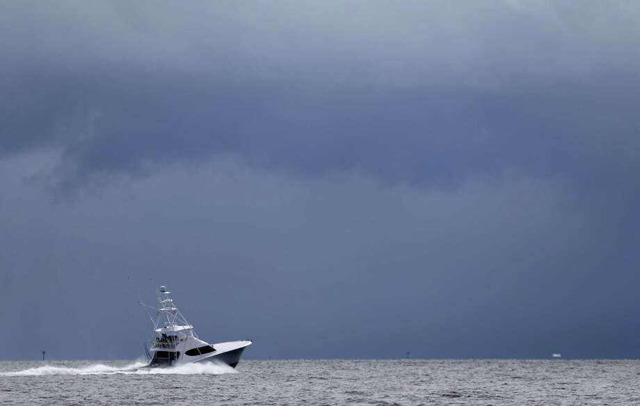 In this Sept. 12, 2014, file photo, a fishing boat heads out to the Atlantic Ocean near Miami as dark clouds loom in the distance. In the annual detailed physical for Earthís climate, scientists noted the world is in increasingly hot and rising water. Photo: AP Photo  / AP