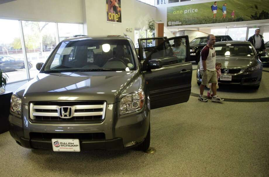 FILE - Buyers look over a 2008 Pilot sports-utility vehicle while a 2008 Accord coupe sits in the background at a Honda dealership in the south Denver suburb of Littleton, Colo., in this Oct. 18, 2007 file photo. Honda is adding nearly 105,000 vehicles to its U.S. recall of driver's side air bag inflators that can explode with too much force. The added vehicles include nearly 89,000 Pilot SUVs from the 2008 model year, as well as about 11,000 Civics from 2004 and another 5,000 Accords from the 2001 model year. (AP Photo/David Zalubowski, FILE) Photo: AP / AP