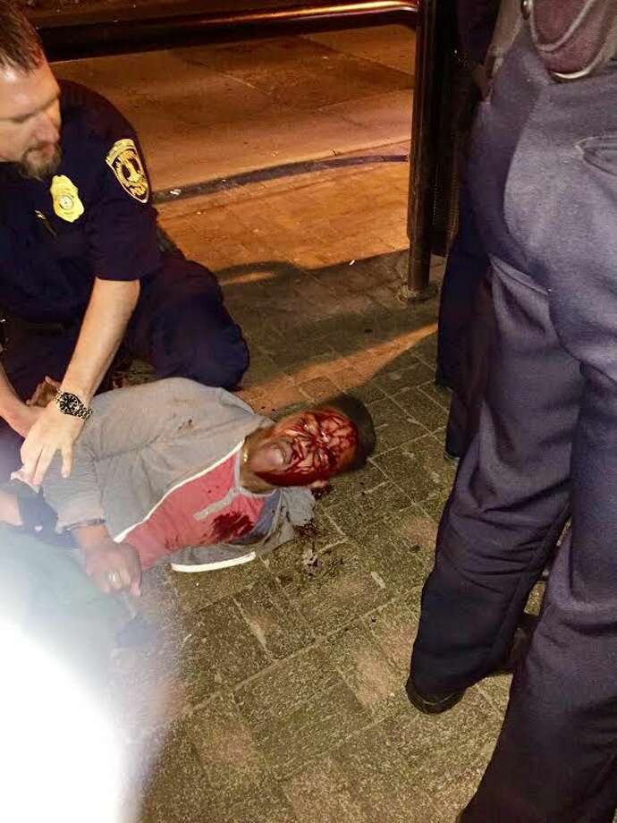 In this photo provided by Bryan Beaubrun, Martese Johnson is held down by an officer Wednesday, March 18, 2015, in Charlottesville, Va. Court records show that Johnson was charged with obstruction of justice without force and public swearing or intoxication. The Virginia Gov. Terry McAuliffe is calling for an investigation into the arrest of the student. (AP Photo/Bryan Beaubrun) Photo: AP / Bryan Beaubrun