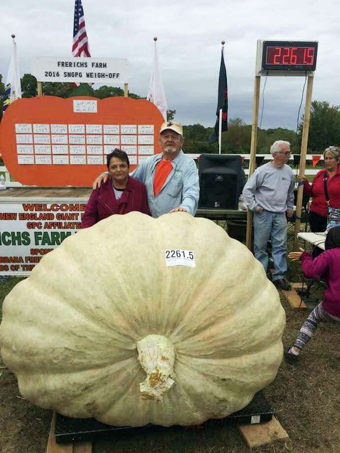 In this Oct. 8, 2016, photo provided by Ron Wallace, Richard and Catherine Wallace stand with a 2,261.5-pound pumpkin that Richard grew to set the North American giant pumpkin record at the Frerichs Farm Pumpkin Weigh Off in Warren, R.I. WJAR-TV reported Richard Wallace's pumpkin beat the record set by his son, Ron, at the same event last year. Photo: Ron Wallace Via AP   / Ron Wallace