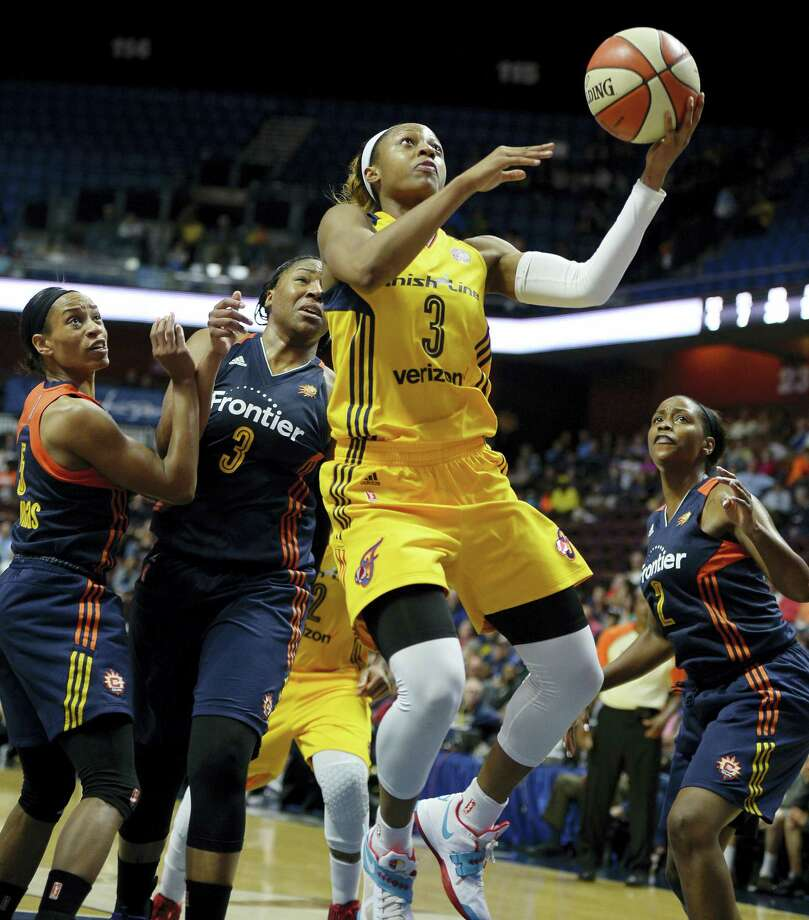 The Fever's Tiffany Mitchell, center, breaks through the Sun's defense during the second half on Sunday. Photo: Jessica Hill — The Associated Press  / AP2016