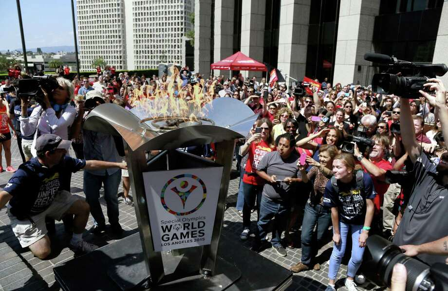 A crowd cheers as torchbearers light the cauldron with the Special Olympic Flame of Hope at South Hope Street Plaza downtown Los Angeles on July 10. Photo: Nick Ut — The Associated Press  / AP