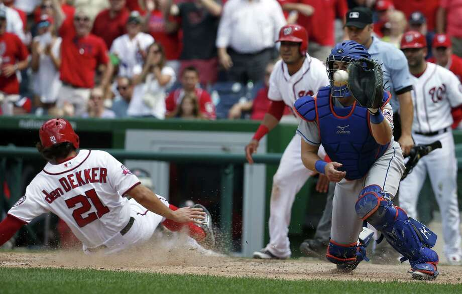 Matt den Dekker slides safely home on a Michael Taylor single as New York Mets catcher Kevin Plawecki waits for the throw during the eighth inning of Wednesday's game at Nationals Park in Washington. The Nats won 3-2. Photo: Alex Brandon — The Associated Press  / AP