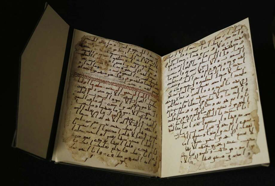 A university assistant shows fragments of an old Quran at the University in Birmingham, in Birmingham central England Wednesday. The University of Birmingham said Wednesday that scientific tests prove a Quran manuscript in its collection is one of the oldest known and may have been written close to the time of the Prophet Muhammad. Radiocarbon testing at Oxford University dated the parchment to the time of the prophet, who is generally believed to have lived between 570 and 632. Photo: AP Photo/Frank Augstein / AP