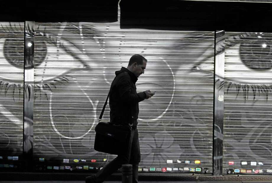 In this 2013 file photo, a man looks at his cellphone as he walks on the street in downtown Madrid. Photo: AP File Photo  / AP