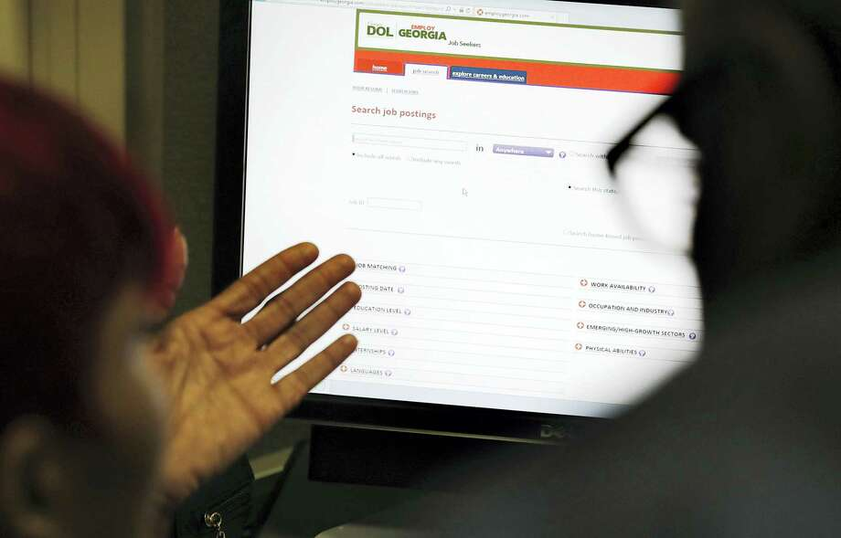 In this March 3, 2016 photo, Georgia Department of Labor services specialist Louis Holliday, right, helps a woman with a job search on a computer at an unemployment office in Atlanta. Photo: AP Photo/David Goldman  / Copyright 2016 The Associated Press. All rights reserved. This material may not be published, broadcast, rewritten or redistributed without permission.