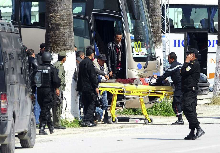 A victim is being evacuated from the Bardo museum are evacuated in Tunis, Wednesday, March 18, 2015 in Tunis, Tunisia after gunmen opened fire at the leading museum in Tunisia's capital. Tunisia's prime minister says 21 people are dead after an attack on a major museum, including 17 foreign tourists ó and that two or three of the attackers remain at large. Photo:  (AP Photo/Hassene Dridi) / AP