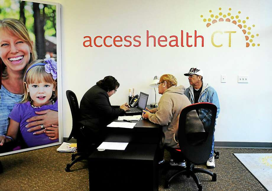 Gildred Ortiz, center and Julio Colon, right, receive help from outreach worker for Access Health CT, Cristela Solorio Ruiz during a grand opening for Connecticut's health insurance exchange's first insurance store on Nov. 7, 2013 in New Britain, Conn. Photo: AP Photo/Jessica Hill  / FR125654 AP
