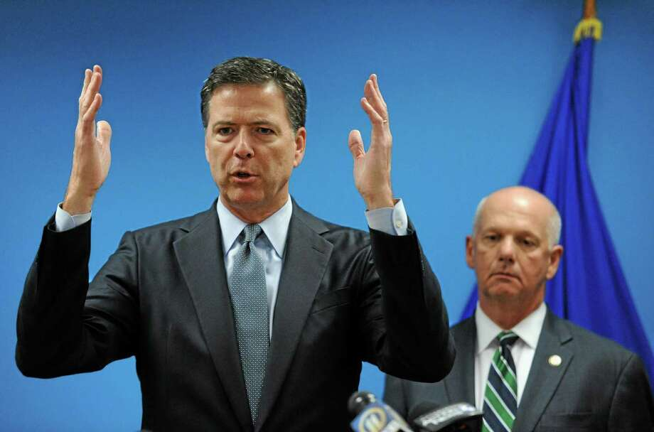 In this July 30, 2014 photo, James Comey, Director of the Federal Bureau of Investigation, left, speaks to the media with U.S. Attorney David J. Hickton at the FBI's Pittsburgh headquarters. Photo: AP Photo/Post-Gazette-Michael Henninger  / Post Gazette