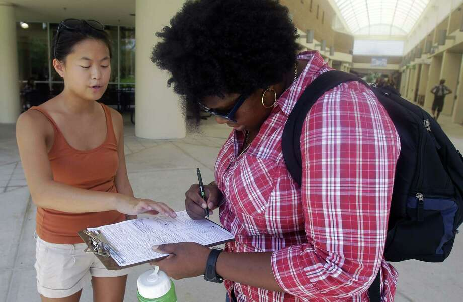 In this July 31, 2012, photo, Aubrey Marks, left, helps a University of Central Florida student to register to vote in Orlando, Fla. Photo: AP File Photo  / AP