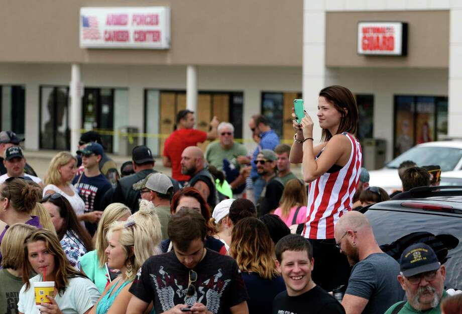 Ashlyn Moore stands on a car bumper Monday to take a photo of the large crowd that gathered at the Lee Highway memorial for last Thursday's Chattanooga, Tenn., shooting victims. Photo: Dan Henry/Chattanooga Times Free Press Via AP   / Chattanooga Times Free Press