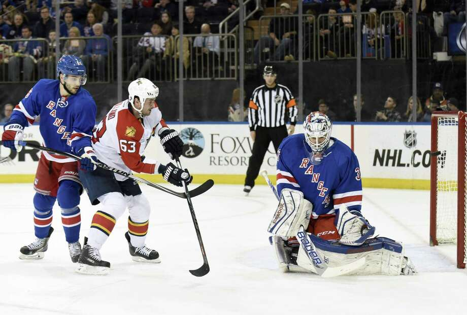 Rangers goalie Cam Talbot, right, deflects a shot by the Florida Panthers' Dave Bolland (63) as Bolland is checked by Derick Brassard during Sunday's game at Madison Square Garden in New York. Photo: Bill Kostroun — The Associated Press  / FR51951 AP