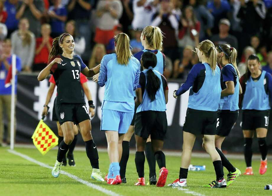 U.S. forward Alex Morgan (13) runs to the bench to celebrate her second goal of the game with teammates during the second half of an International friendly against Japan on Thursday. Photo: Jack Dempsey — The Associated Press  / FR42408 AP