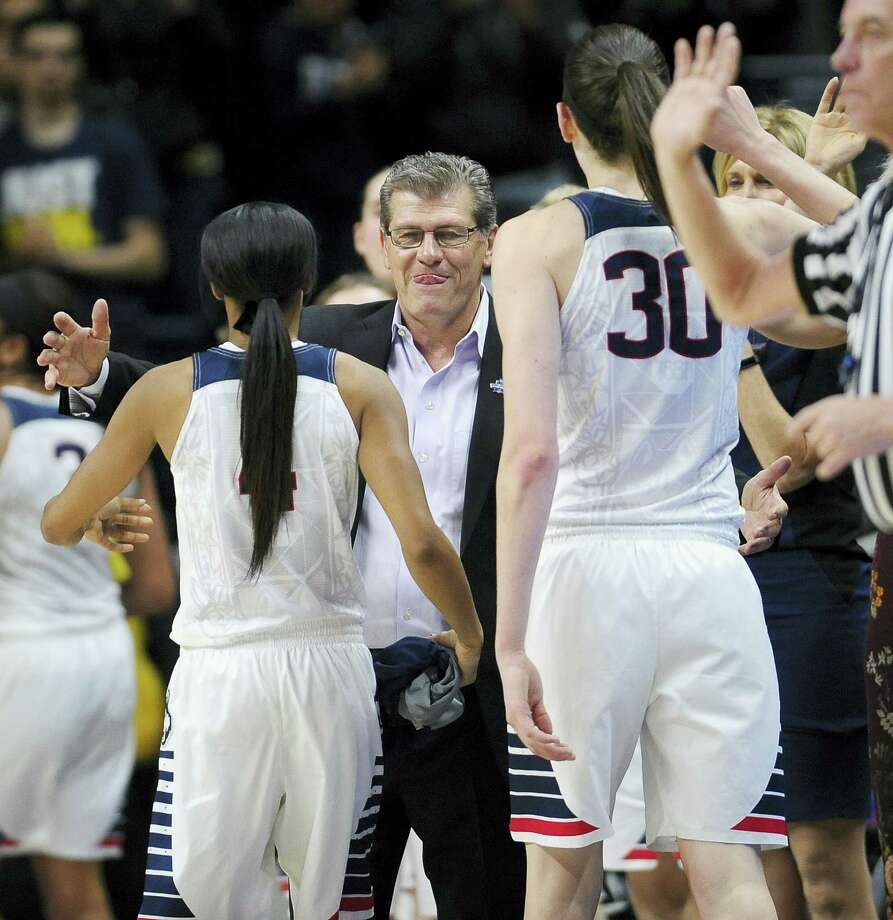 UConn head coach Geno Auriemma reaches his arms out to seniors Moriah Jefferson, left, and Breanna Stewart after they finish in the second half of Monday's 97-51 against Duquesne. Photo: Jessica Hill — The Associated Press  / AP2016