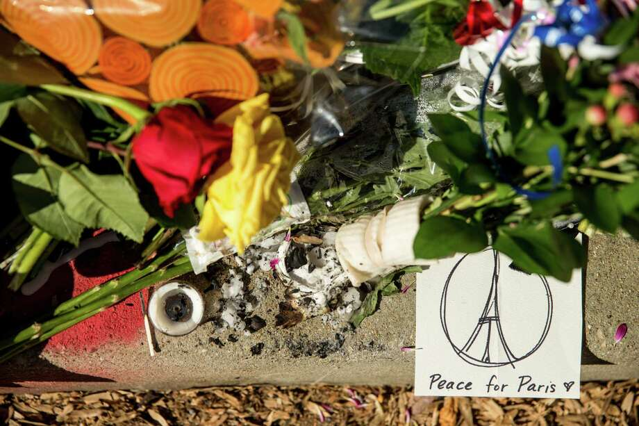 Mourners leave flowers and cards outside the gates of the French Embassy in Washington on Nov. 15, 2015. Photo: AP Photo/Andrew Harnik  / AP