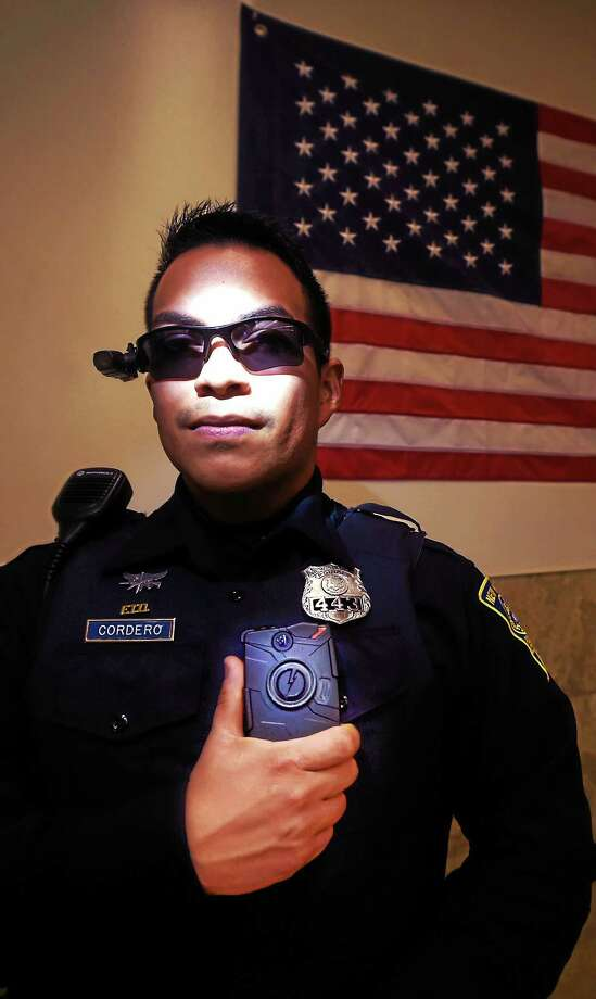 New Haven Police Officer Jeremy Cordero wears sunglasses equipped with a police body camera and also holds a body camera attached to his uniform. The body cameras are part of an  NHPD pilot program testing three different body cameras.  Friday November 13, 2015. Photo: (Peter Hvizdak - New Haven Register)  / ©2015 Peter Hvizdak